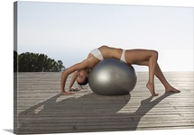 Woman performing yoga on fitness ball