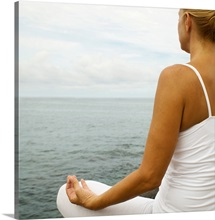 Woman practising yoga by ocean, close up, rear view
