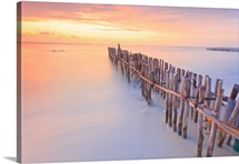 Wooden posts in Caribbean sea, during very colorful sunset.