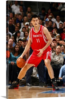 Yao Ming 11 of the Houston Rockets moves the ball against the Denver Nuggets