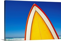 Yellow and orange retro surfboard at beach, Eyre Peninsula, South Australia.