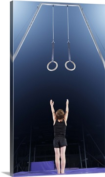 Young male gymnast reaching up to rings