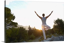Young man balancing on rock in mountain landscape, rear view