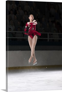Young woman figure skater mid-air performing a triple axel