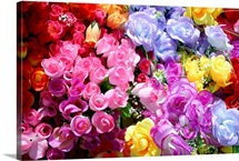 A bright and colorful array of silk flowers at an outdoor flea market