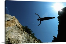 A cliff diver silhouetted in flight against a blue sky