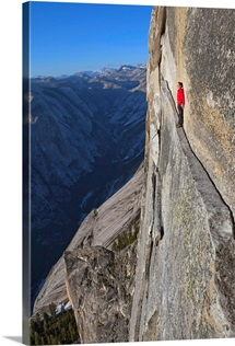 A climber walks a 40-foot-long sliver of granite on Half Dome, named the Thank God Ledge