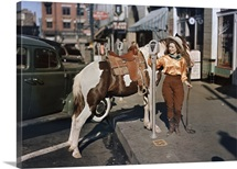 A cowgirl puts a nickel in an El Paso parking meter to hitch her pony