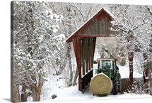 A farmer in a tractor crossing a covered bridge during a winter snow