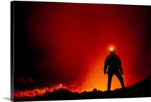 A geologist silhouetted by glowing lava