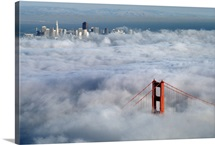A glowing tower of the Golden Gate Bridge rises above the fog, San Francisco Bay, California