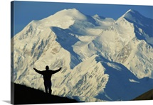 A hiker silhouetted against snow covered Mount McKinley