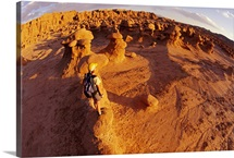 A hiker views the rock formations at Goblin Valley