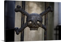 A macabre detail from the fence of an old tomb