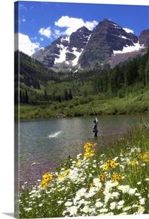 A man fishing in a scenic mountain lake near the Maroon Bells peaks