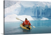 A man in a kayak explores an iceberg near Peterman Island