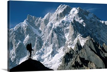 A man stands silhouetted against the Karakoram Mountains, Pakistan