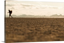 A man walks with a heavy backpack across a dry Colorado River delta