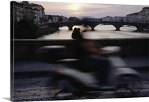 A motorcyclist passes a couple kissing on a bridge, Florence, Italy