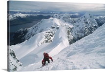 A mountain climber scrambles up a steep, rime covered slope