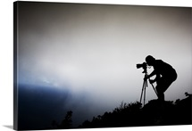 A photographer sillhouetted against thick clouds atop Mount Scenery