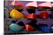 A rack of colorful kayaks awaits paddlers