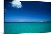A sailboat plies a clear blue sea under sky with a single cloud, Cuba