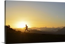 A silhouetted man running near the Verdon Gorge at twilight