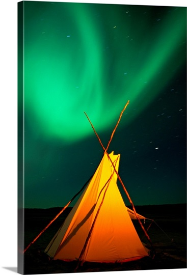 A solitary tepee is illuminated under a sky streaked with light from the aurora borealis, Northwest Territories, Canada