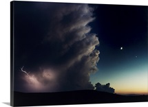 A thunderstorm, evening star, and crescent moon collide on a hilltop