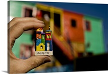 A tiny souvenir is echoed by the real buildings of colorful La Boca