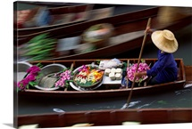 A vendor with flowers and other goods at the floating market