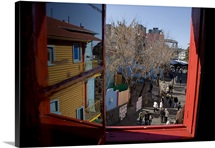 A window frames and reflects colorful La Boca