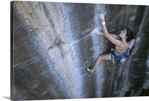 A woman climbs a sheer rock cliff in Moab