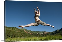A young women leaps through the air on a clear summer day