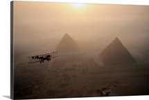 Airplane flies above pyramids during a golden sunrise at Giza, Egypt