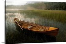 An Adirondack guide canoe floats on Connery Pond at sunrise