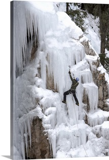 An ice climber climbing with an ice axe on a frozen waterfall