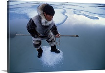 An Inuit hunter on an ice floe waiting for a ringed seal to appear