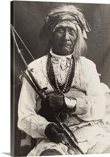 An old war chief, seated on a chair, poses with a bow and arrows