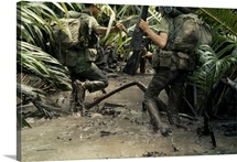 Armed South Vietnamese marines slog through jungle mud