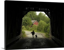 Child and dog walking from a covered bridge, U.S