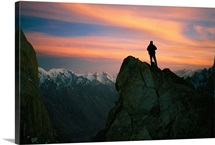 Climber watches sunset over the Karakoram Mountains, Trango Towers, Karakoram Mountains, Pakistan