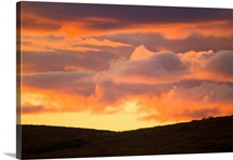 Colorful cumulus clouds above hills in fall tundra at sunset