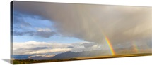 Cumulus clouds and rainbow over tundra and distant snowy Alaskan Range