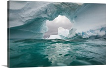 Floating icebergs, ice arch and sea waves seen from water&amp;#39;s surface