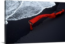 Lady in flowing red on a black sand beach at surfs edge in Iceland