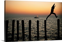 Man leaping between pilings in the Chesapeake Bay off Great Fox Island, Virginia