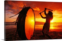 Native Hawaiian beating drum on Makena beach at sunset, Maui, Hawaii