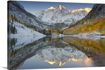 Reflections of snow-covered mountains and golden aspen trees in a lake